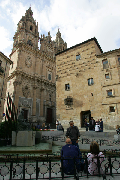 """People chat in front of the historical monuments """"La Casa de las Conchas"""" (R) and """"La Clerecia"""" in Salamanca, 11 October 2005. The XV Ibero-American summit will take place on Friday and Saturday in this northern Spanish city. AFP PHOTO/PHILIPPE DESMAZES"""