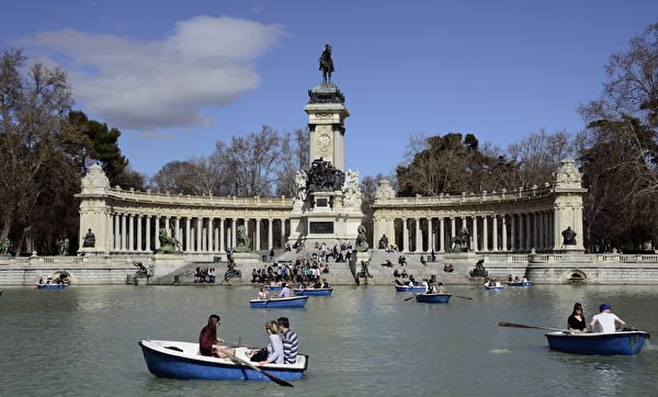 People row rented boats on the artificial lake in Madrid's Retiro Park in on March 27, 2015. AFP PHOTO/ GERARD JULIEN