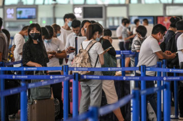 Passengers wait in line in the counter area following preventive procedures against the spread of the COVID-19 coronavirus in Pudong International Airport in Shanghai on June 11, 2020. (Photo by Hector RETAMAL / AFP) (Photo by HECTOR RETAMAL/AFP via Getty Images)